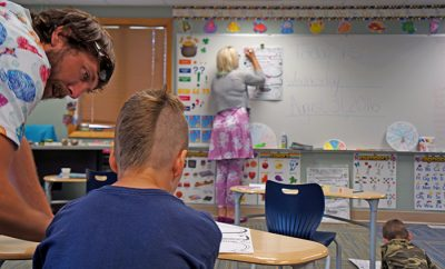 Yellowstone Academy staff work with students in the remodeled classroom on the first day of school.